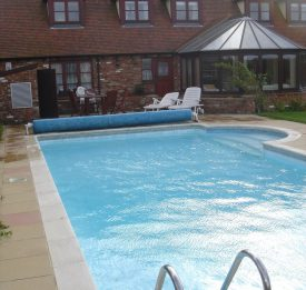 Outdoor residential pool with heat retaining cover